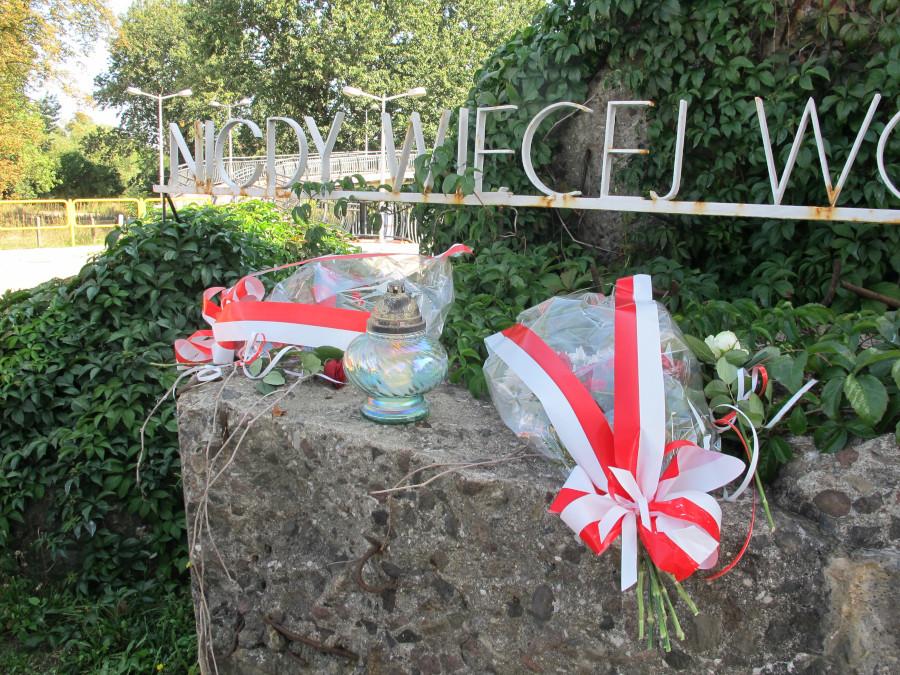 """Kwiaty i znicze pod pomnikiem """"Nigdy więcej wojny"""" w Augustowie"""