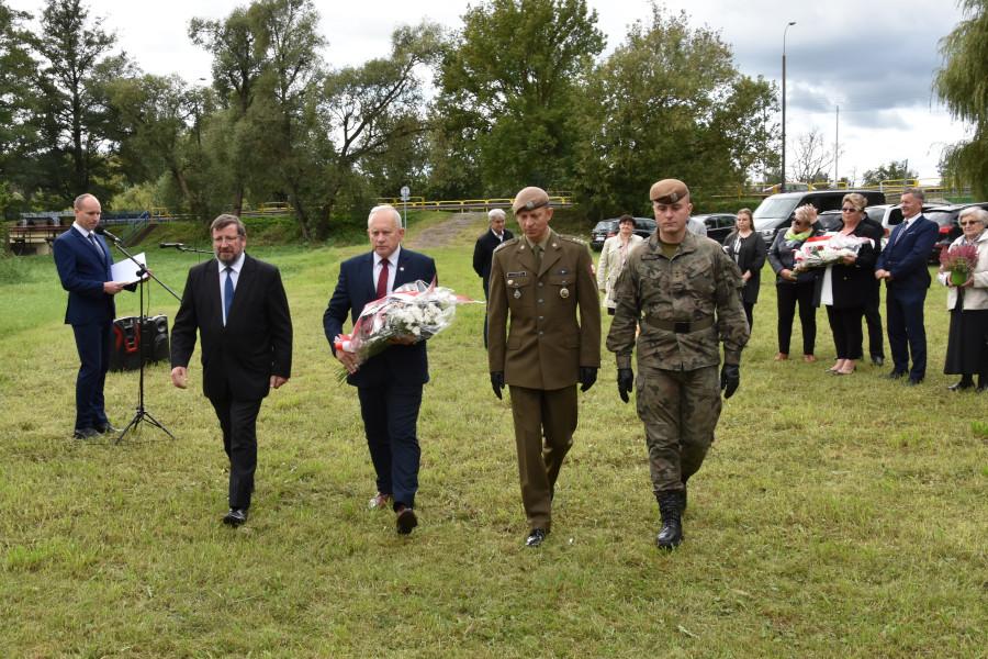 Delegacja składająca wiązankę pod pomnikiem w Białobrzegach w dn. 17 września, od lewej: Zbigniew Kaszlej, Jarosław Szlaszyński – Starosta Augustowski, przedstawiciele 12 Batalionu Lekkiej Piechoty Wojsk Obrony Terytorialnej.