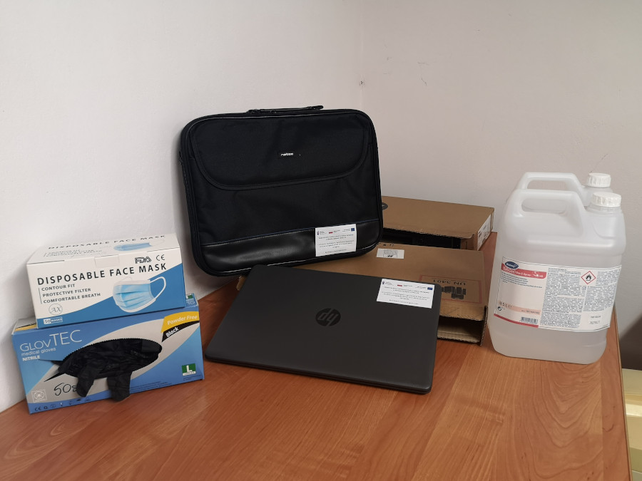 Na zdjęciu zakupiony sprzęt i akcesoria. Od lewej maseczki i rękawiczki ochronne, komputer typu laptop z torbą do przenoszenia oraz płyn do dezynfekcji.