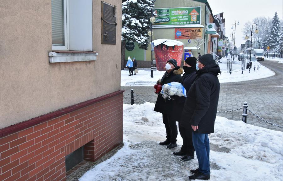 Delegacja Powiatu Augustowskiego na skrzyżowaniu ul. Mostowej z Rynkiem Zygmunta Augusta (przy przychodni Lider w Augustowie) składająca wiązankę kwiatów pod tablicą